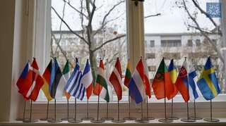 Flags of the members of the European Centre of Excellence for Civilian Crisis Management in front of a window